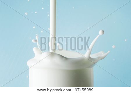 Splash of milk in glass on blue background
