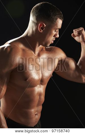 Male bodybuilder looking at his flexing muscles, close-up