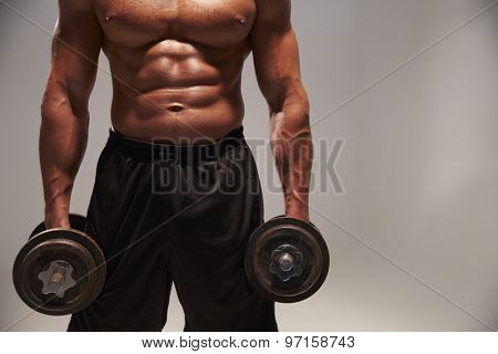 Male bodybuilder working out with heavy dumbbells, with copy space