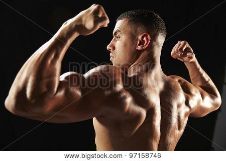 Male bodybuilder flexing muscles, side view