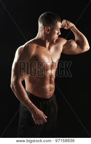 Male bodybuilder looking at his flexing muscles