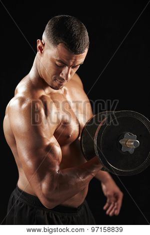 Muscular young man working out with  heavy dumbbell