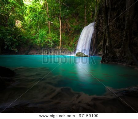 Waterfall flows into lake in forest and sunlight shines through trees and leaves