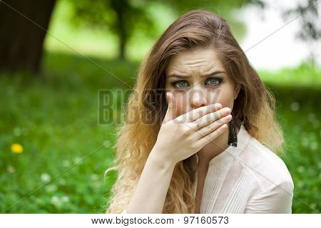 Young beautiful girl covers her mouth with his hand, posing outdoors in summer park