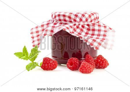 jar of raspberry jam with stray fruits and mint leaves isolated on white background