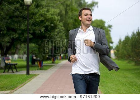 Handsome young man in gray suit walking in the summer park