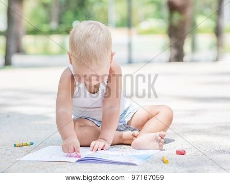 Cute baby is painting outdoor