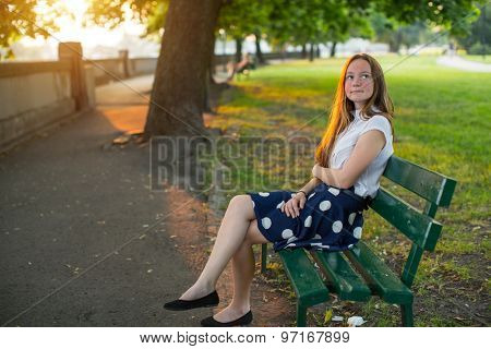 Cute young girl with long golden hair sitting alone on a bench in the Park.