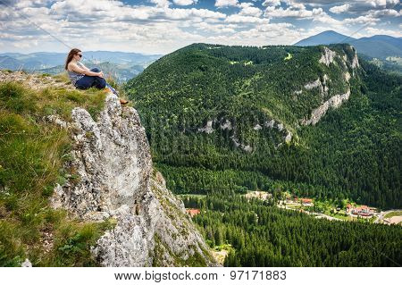 Young woman is sitting at the edge of cliff in mountains. Lacu Rosu AKA Red Lake area, Carpathians, Romania