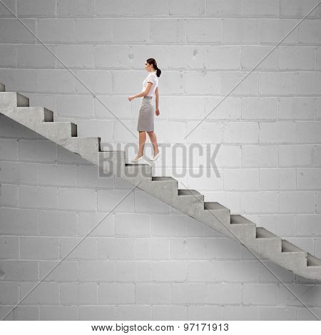 Young businesswoman walking up on staircase representing success concept
