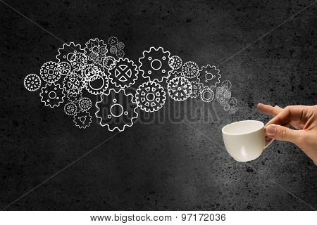 Hand holding coffee cup with gears coming out