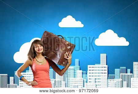 Traveler woman walking with retro suitcase on shoulder