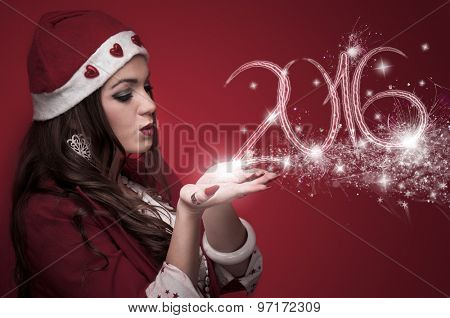 Woman in Santa costume blowing stars and made New year numbers 2016