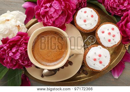 Composition with cup of coffee, muffins and peony flowers on wooden background