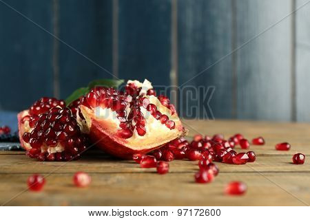 Pomegranate seeds on wooden table, closeup