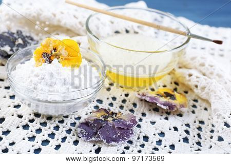 Making candied violet flowers with egg whites and sugar, on color wooden background
