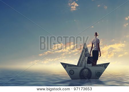 Businesswoman escapes from the crisis on a paper boat