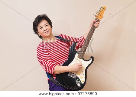 Portrait Of Adult Asian Woman With Electric Guitar, Warm Toned, Studio Shot
