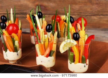 Snack of vegetables in glassware on tray on wooden background