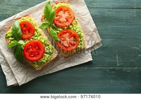 Vegan sandwich with avocado and vegetables on wooden background