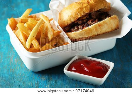 Tasty burger and french fries on wooden table background  Unhealthy food concept