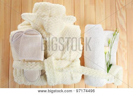 Bathrobe, towel and slippers on wooden table, top view