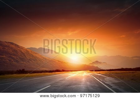 Empty asphalt road and sun rising at skyline