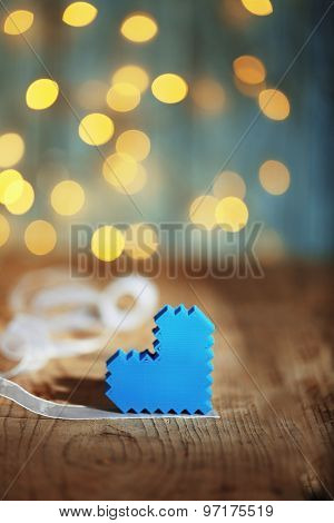 Heart on wooden table and blurred background with lights