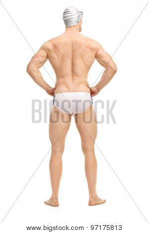 Full length rear view shot of a handsome male swimmer in white swim trunks and a gray swim cap isolated on white background