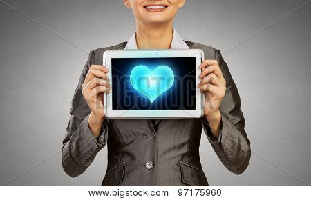 Young businesswoman showing tablet pc against heart