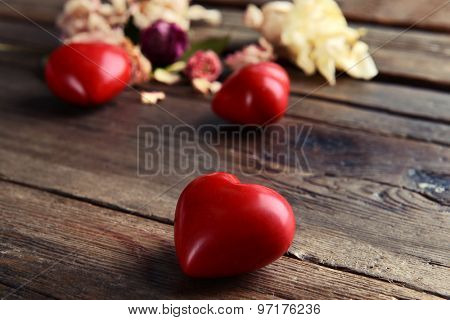 Decorative hearts with dry flowers on wooden table close up