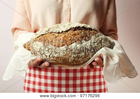 Woman holding tasty fresh bread, close up