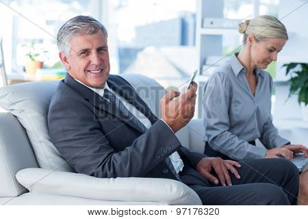 Smiling businessman on call while his secretary looks at laptop in office