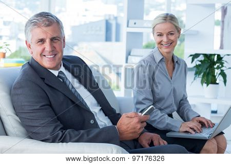 Smiling businessman and his secretary looking at camera in office