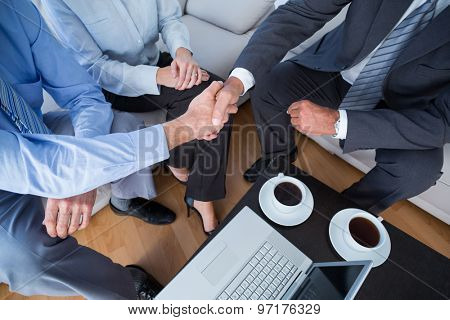Three business people with laptop and hot beverages at office