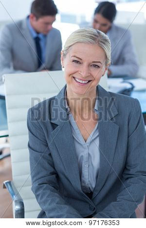 Smiling businesswoman looking at camera in an office