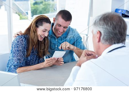 Happy couple looking at ultrasound scan of their baby in medical office