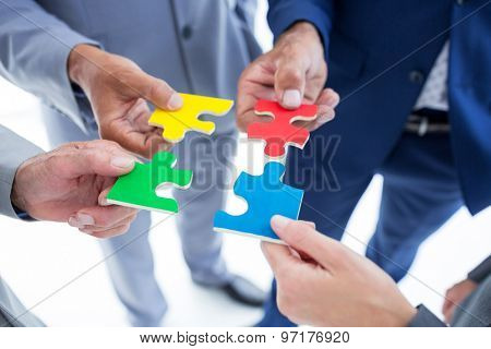 Business colleagues holding piece of puzzle in the office