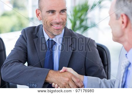 Businessman handshaking colleague in the office
