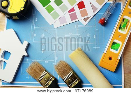 Construction instruments, plan, color samples and brushes on wooden table background