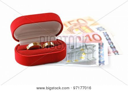 Wedding rings in box on banknotes, isolated on white background. Marriage of convenience
