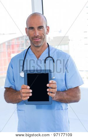 Smiling doctor holding tablet computer in medical office