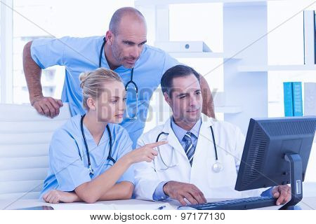 Teams of doctors working on laptop computer in medical office