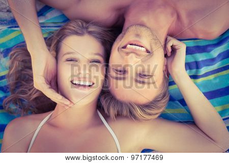 Beautiful couple smiling a the camera at the beach