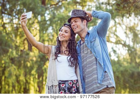 Hipster couple taking a selfie on a sunny day