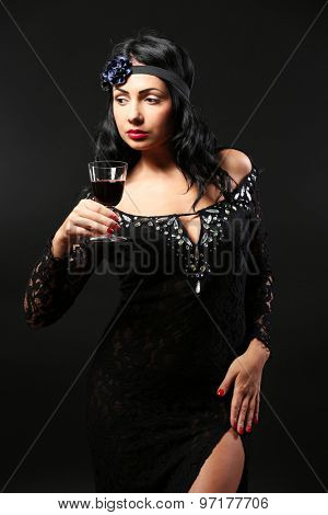 Pretty elegance woman with wineglass on black background
