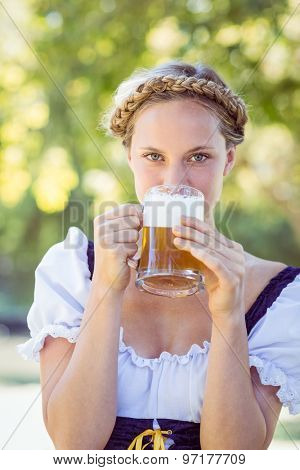 Pretty oktoberfest blonde drinking in the park on a sunny day