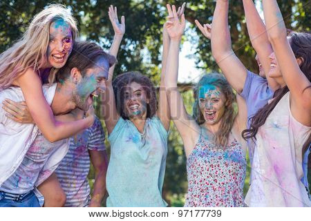 Happy friends covered in powder paint on a sunny day