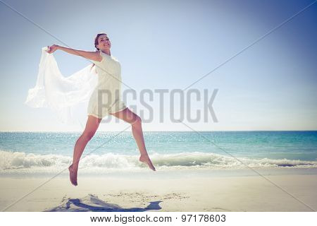 Peaceful brunette jumping at the beach on a sunny day