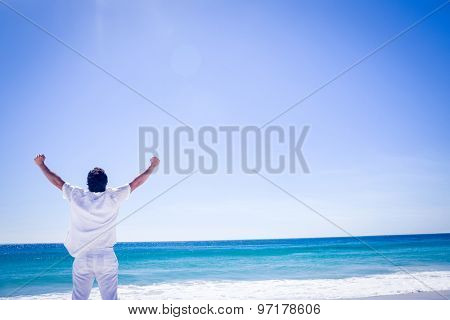 Man stretching his arms in front of the sea at the beach